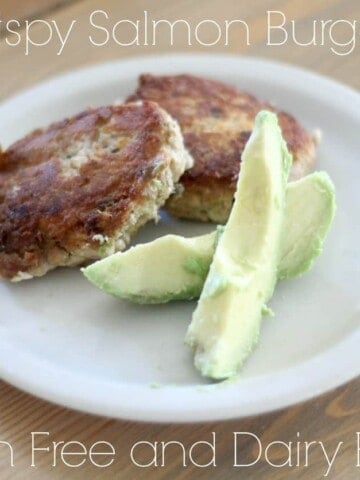 salmon burger on a white place with sliced avocado
