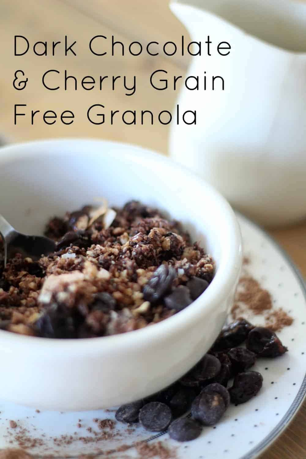 a white bowl filled with grain-free granola with chocolate chips and cherries on a silver and white polka dot plate