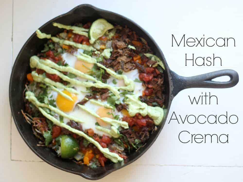 cast iron skillet with Mexican hash browns topped with eggs and avocado cream