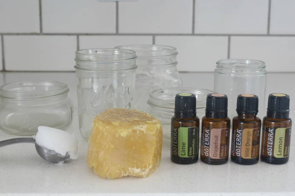 beeswax, coconut oil, essential oil and mason jars on a white countertop