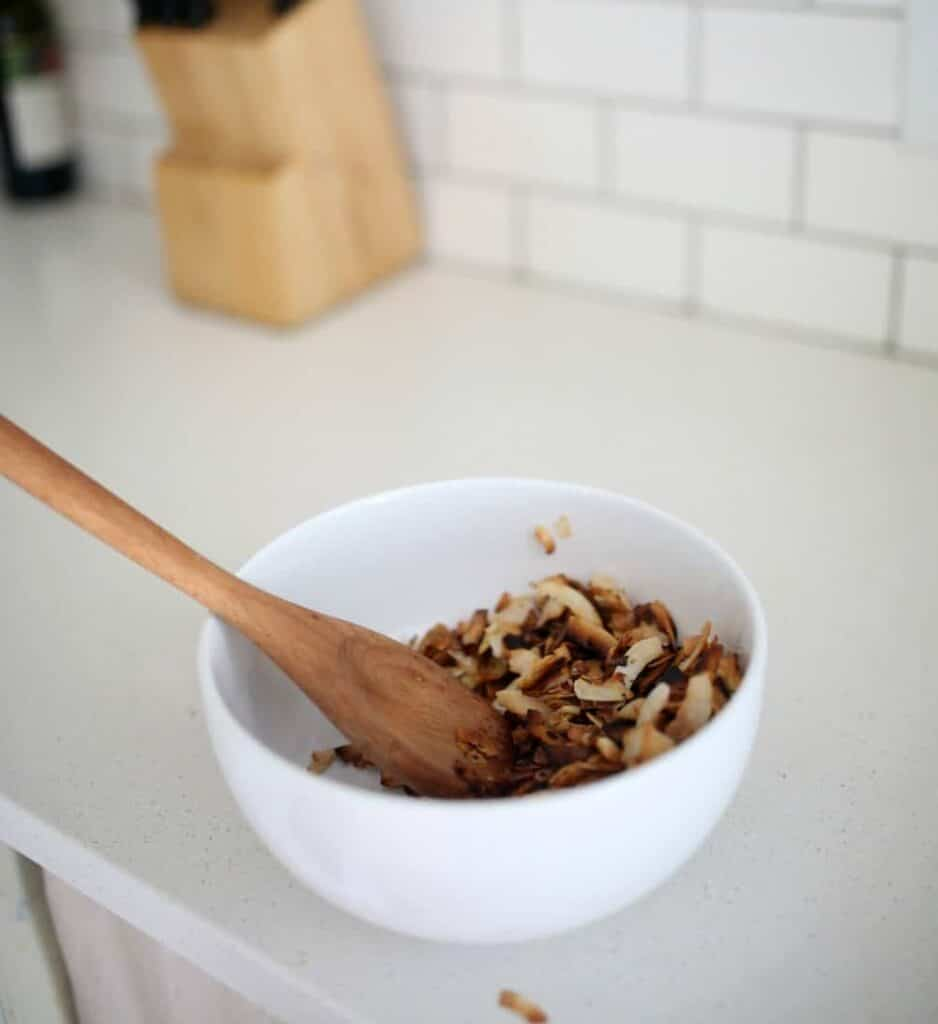 Toasted coconut chips in a white bowl with a wooden spoon on a white quartz countertop