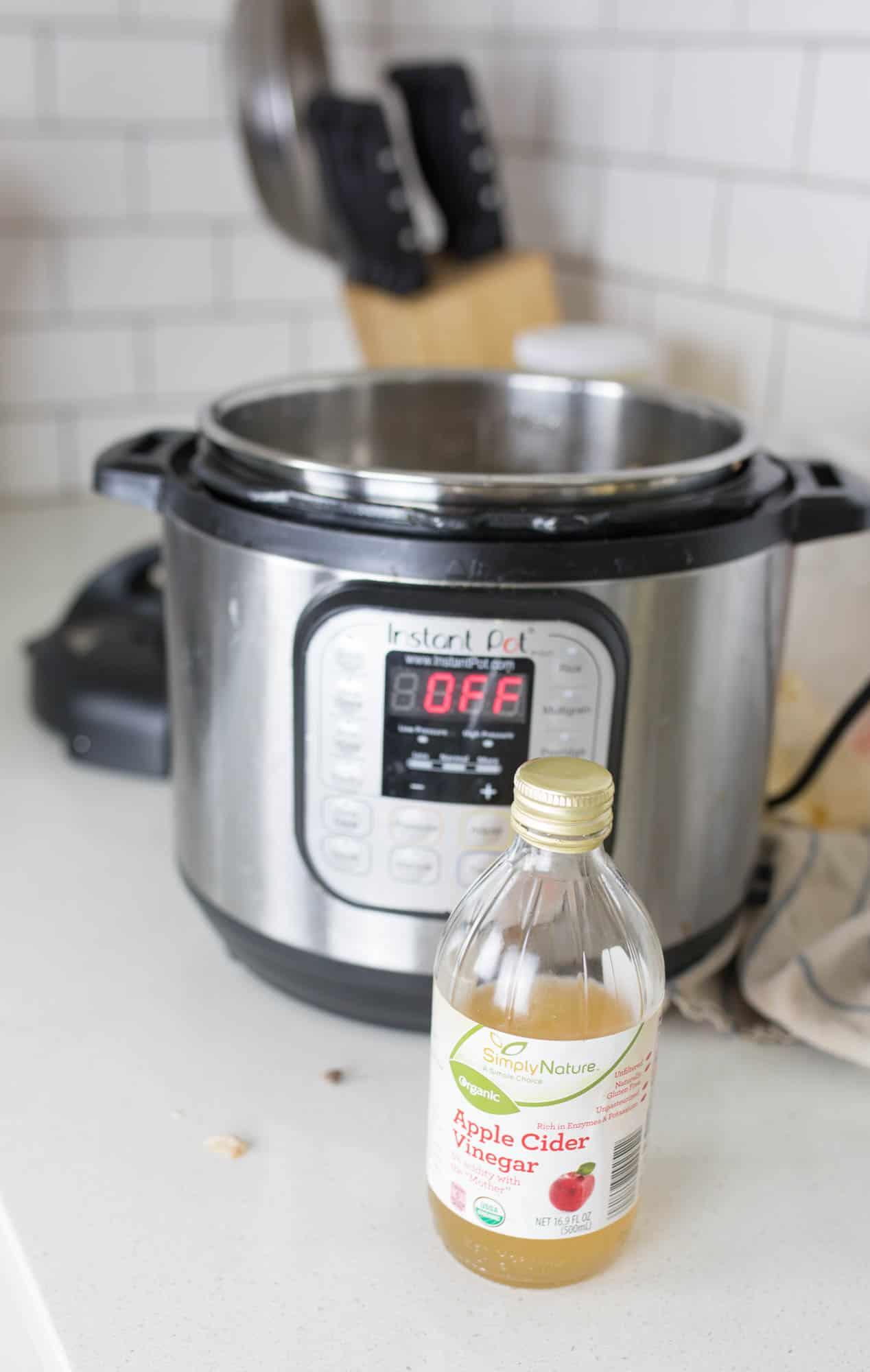 instant pot on a white countertop with a bottle of apple cider vinegar in front of it