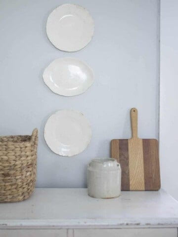 farmhouse plates hanging on a wall above a dresser
