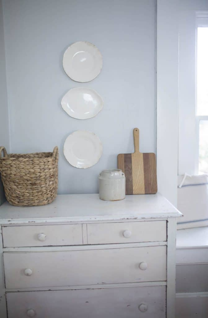 white stoneware plates hanging on a wall - how to hang plates on a wall tutorial