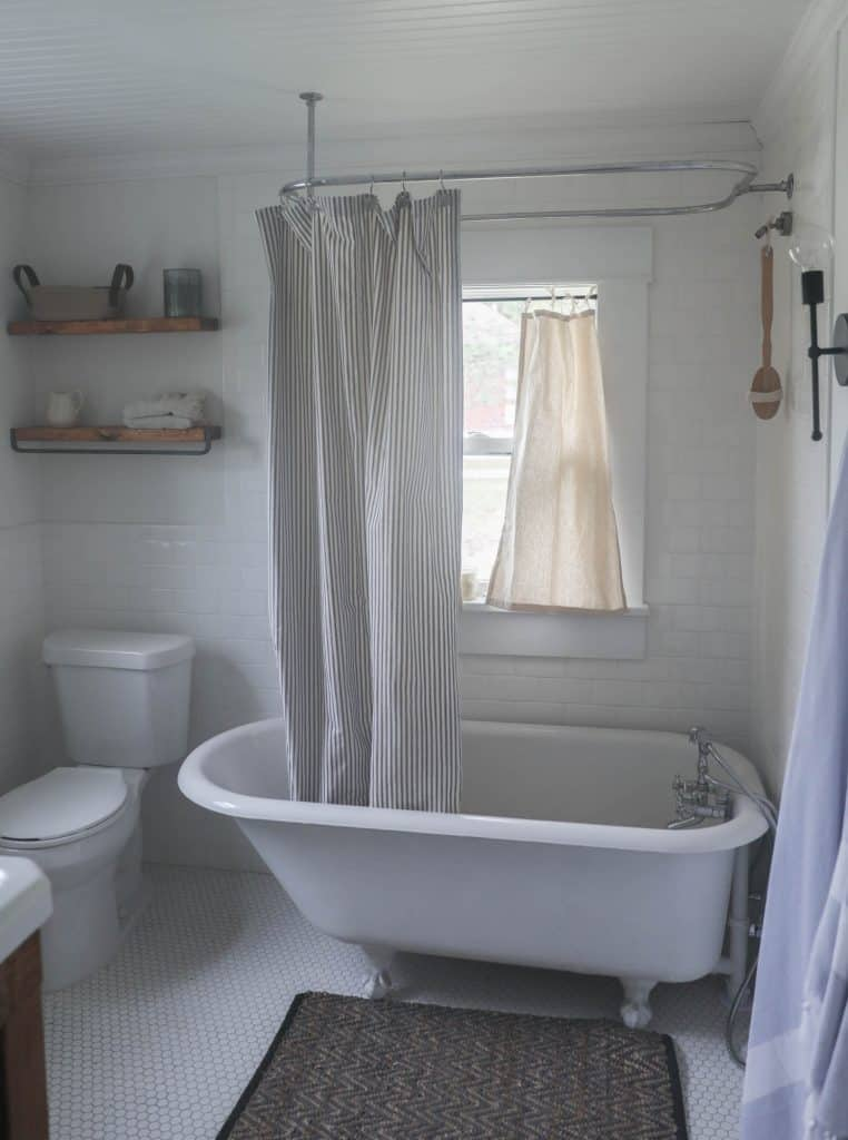 drop cloth curtains hanging in a window over a bathtub in a farmhouse bathroom with a claw foot tub
