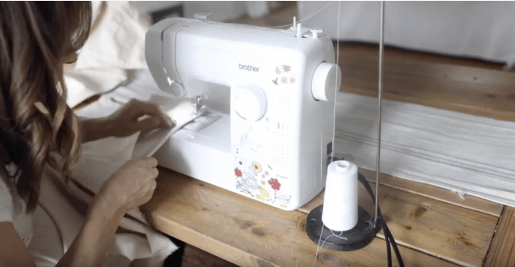 women hemming drop cloth on a white sewing machine with flowers to make drop cloth curtains