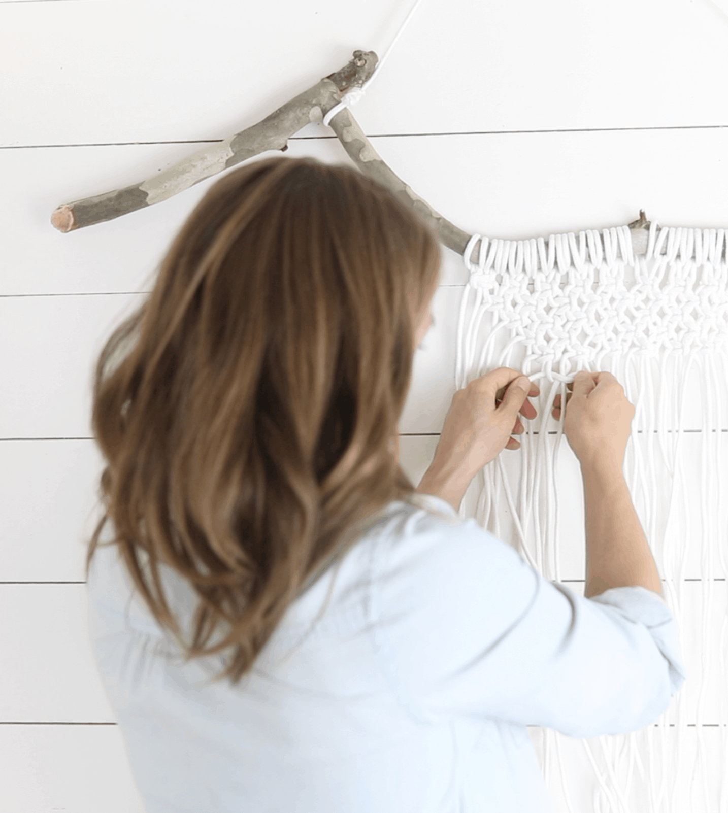 women tying macrame on a wood branch for a diy macrame wall hanging