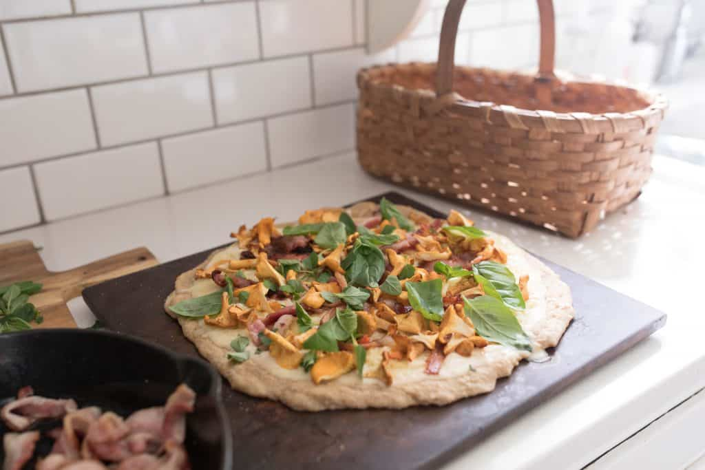 bacon chanterelle sourdough pizza topped with fresh herbs on a pizza stone ready for the oven