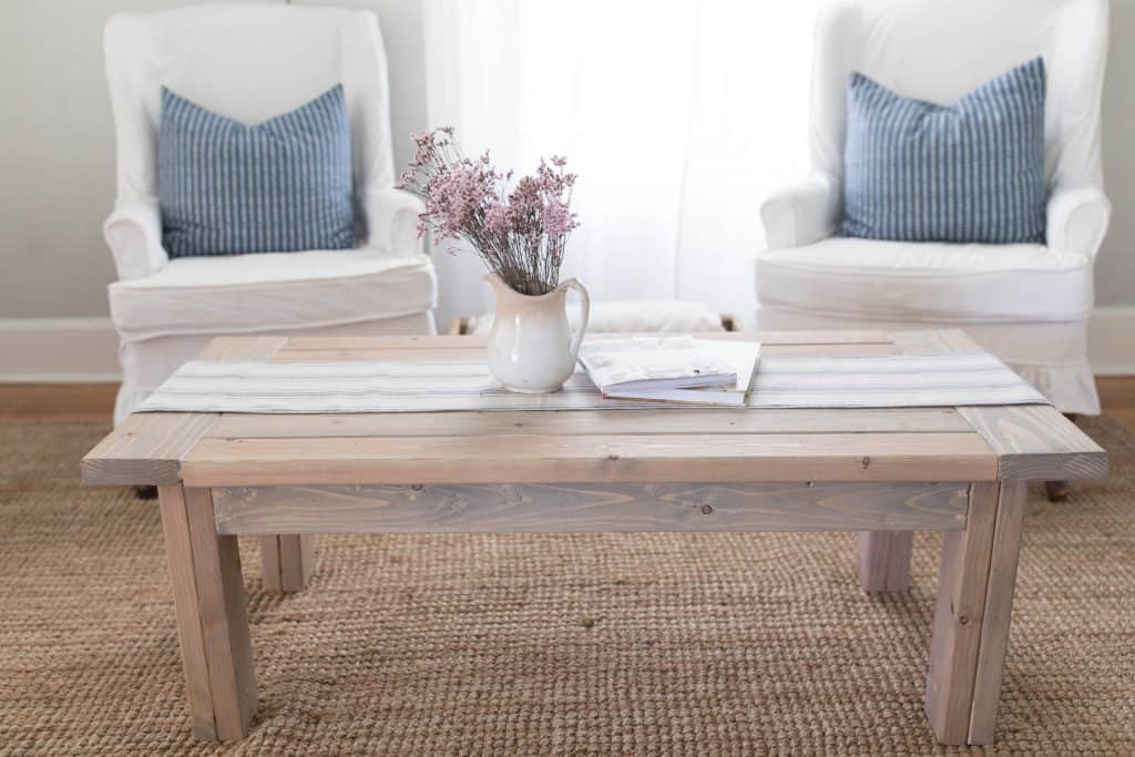 farmhouse coffee table with table runner and a vase of flowers- diy coffee table plans