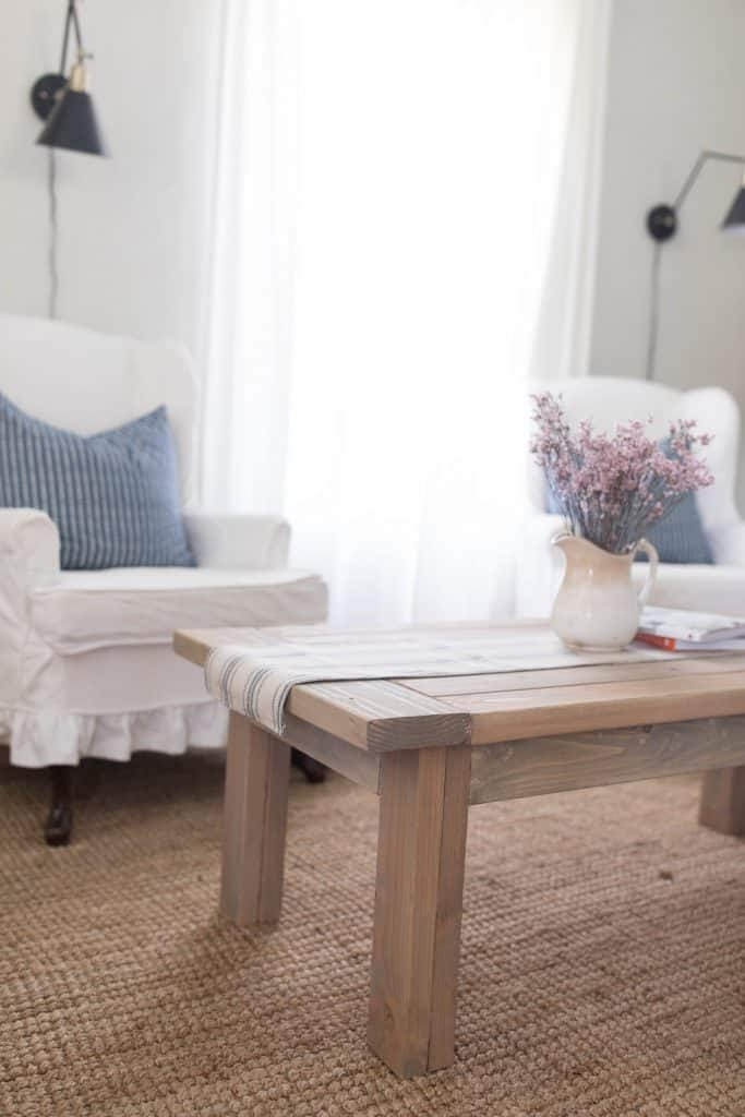 farmhouse coffee table with two white chairs with blue pillows behind it
