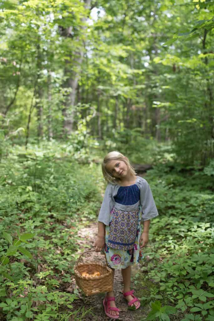 little girl in the woods holding a basket of wild chanterelle mushrooms from foraging