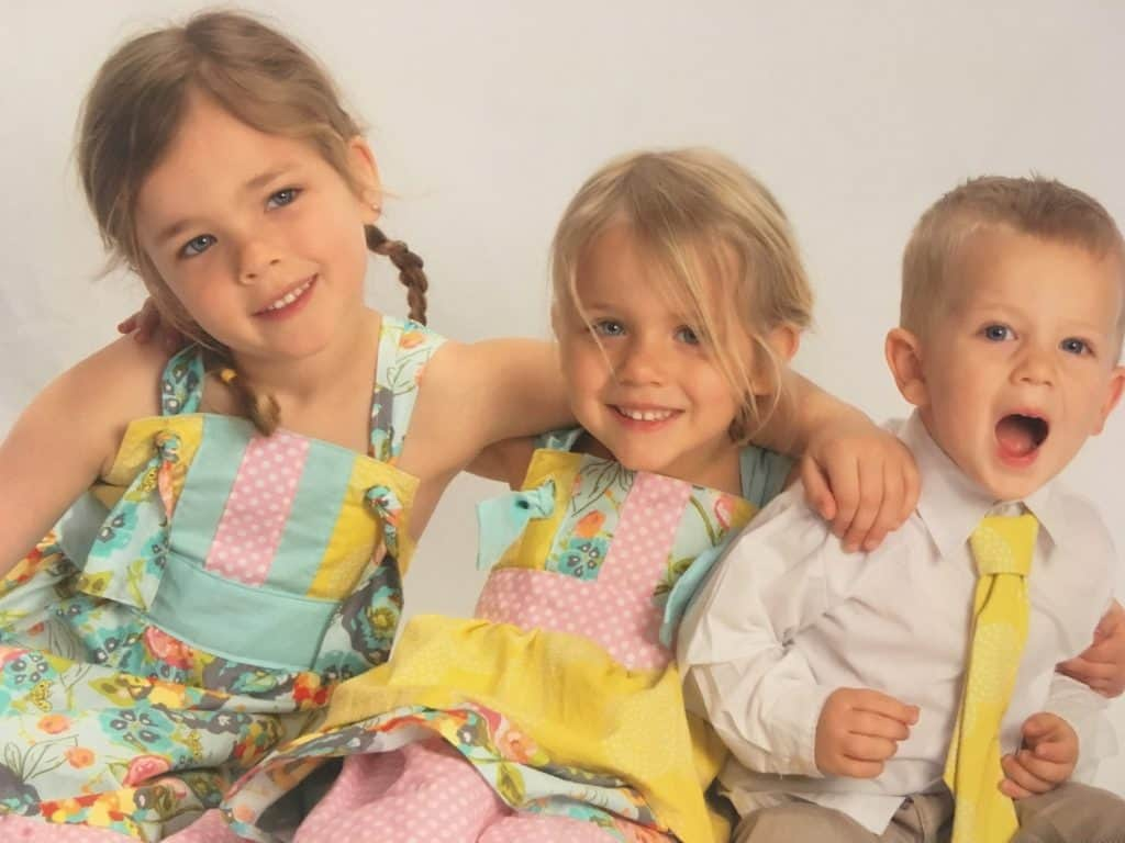 two little girls wearing homemade dresses and a little boy wearing a matching tie