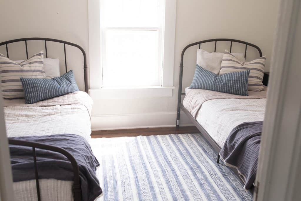 farmhouse boys room makeover iron beds blue tan ticking stipe benjamin moore soft chamois