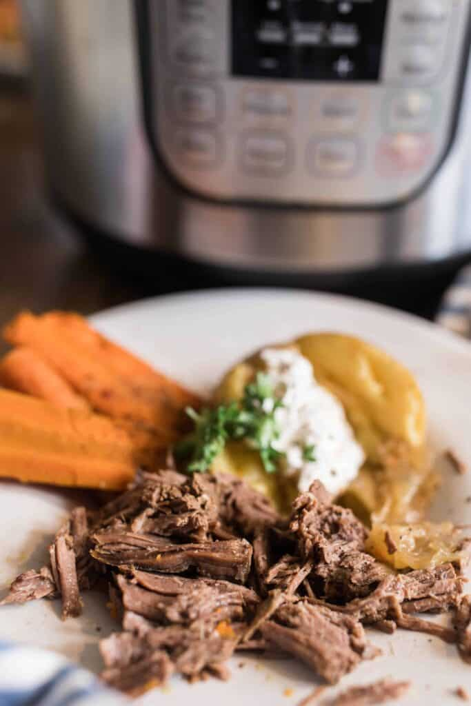tender pot roast shredded on a white plate with carrots and potatoes.