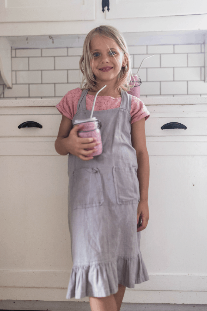 girl with blond hair wearing an apron drinking a berry kefir smoothie in a mason jar