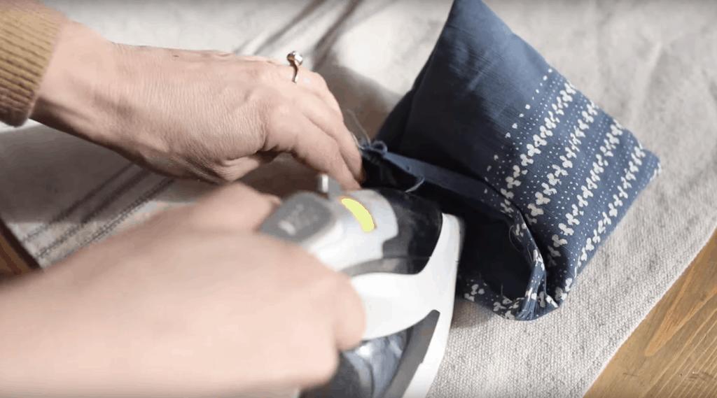 ironing raw edges down on fabric to sew a hem