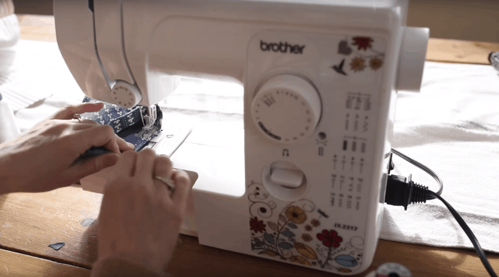 sewing the hem on a white sewing machine with flowers