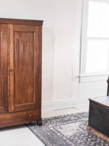 farmhouse style bedroom painted floors antique armoire blue rug chandelier