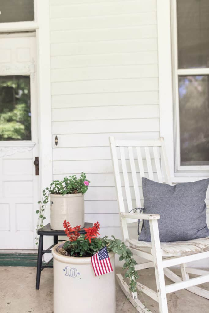 ferns and flowers in crocks and a white chair with blue pillow on a farmhouse front porch