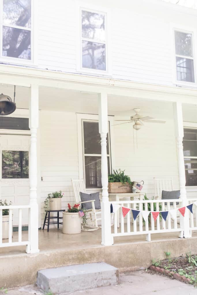 farmhouse summer porch decorated for fourth of july with bunting, crocks full of flowers and ferns and white farmhouse furniture
