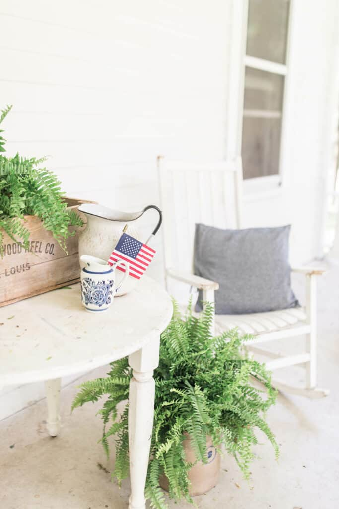 white farmhouse table with ferns in a vintage crate and vintage pitchers on top,