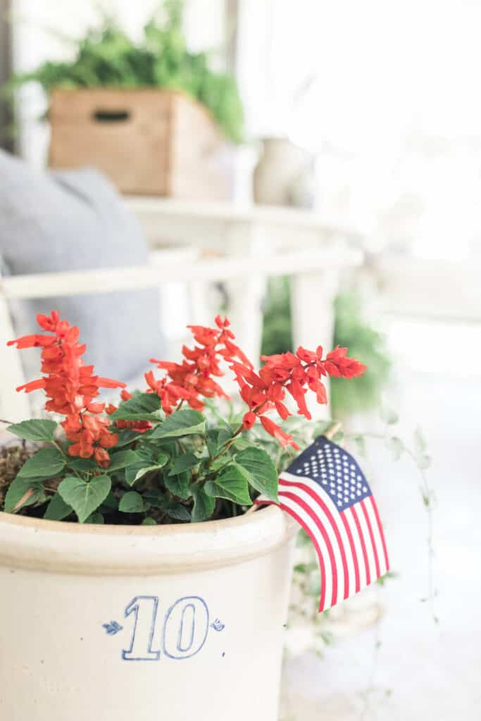 scarlet sage salvia in a crock with an american flag with a rocking chair behind it