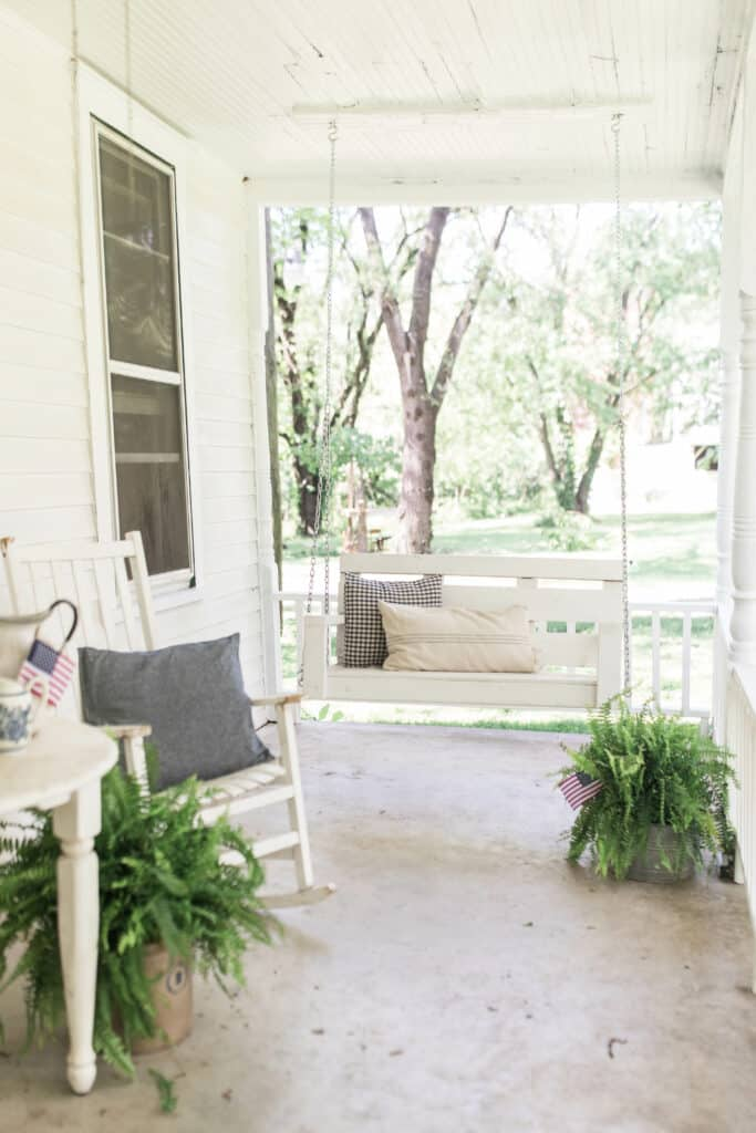 porch swing with farmhouse pillows, a rocking chair to the left with a blue pillow