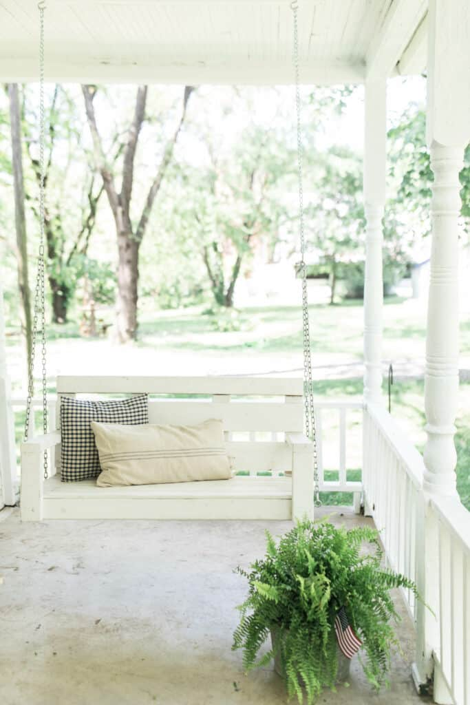 farmhouse pillows on a white porch swing