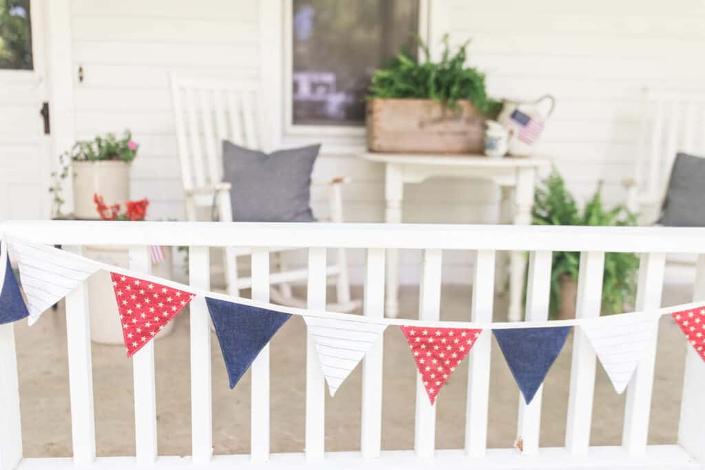 farmhouse front porch with white furniture, blue pillows, forth of July bunting, and plants