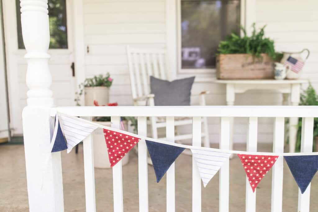 red, white, and blue bunting hanging from a white porch railing with white porch furniture behind it and ferns