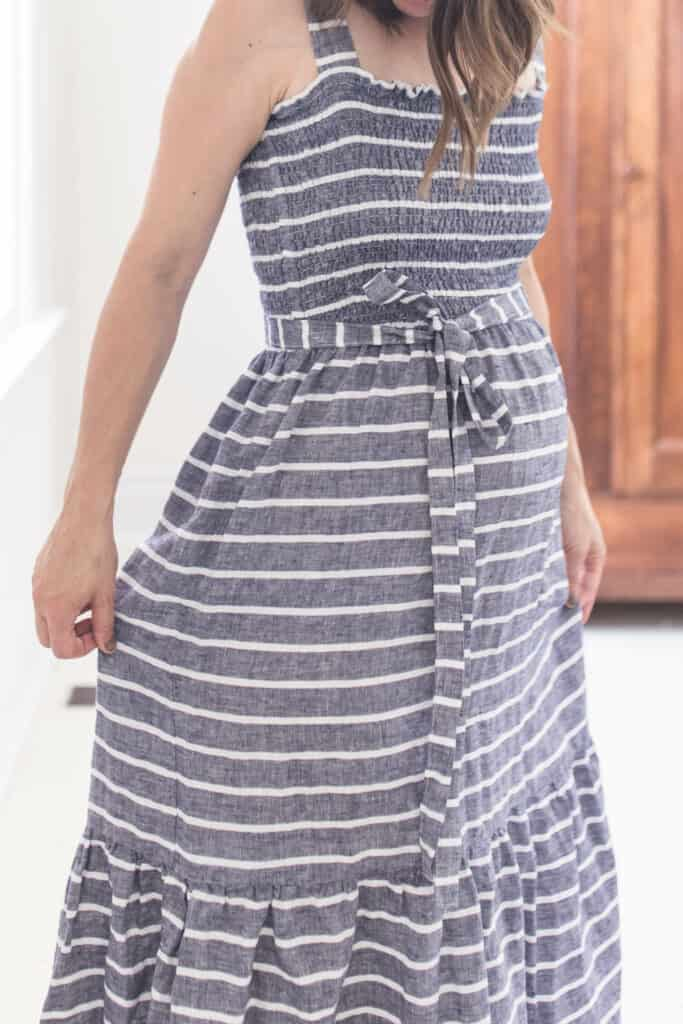 Pregnant women wearing a gray and white stripped shirred dress with belt