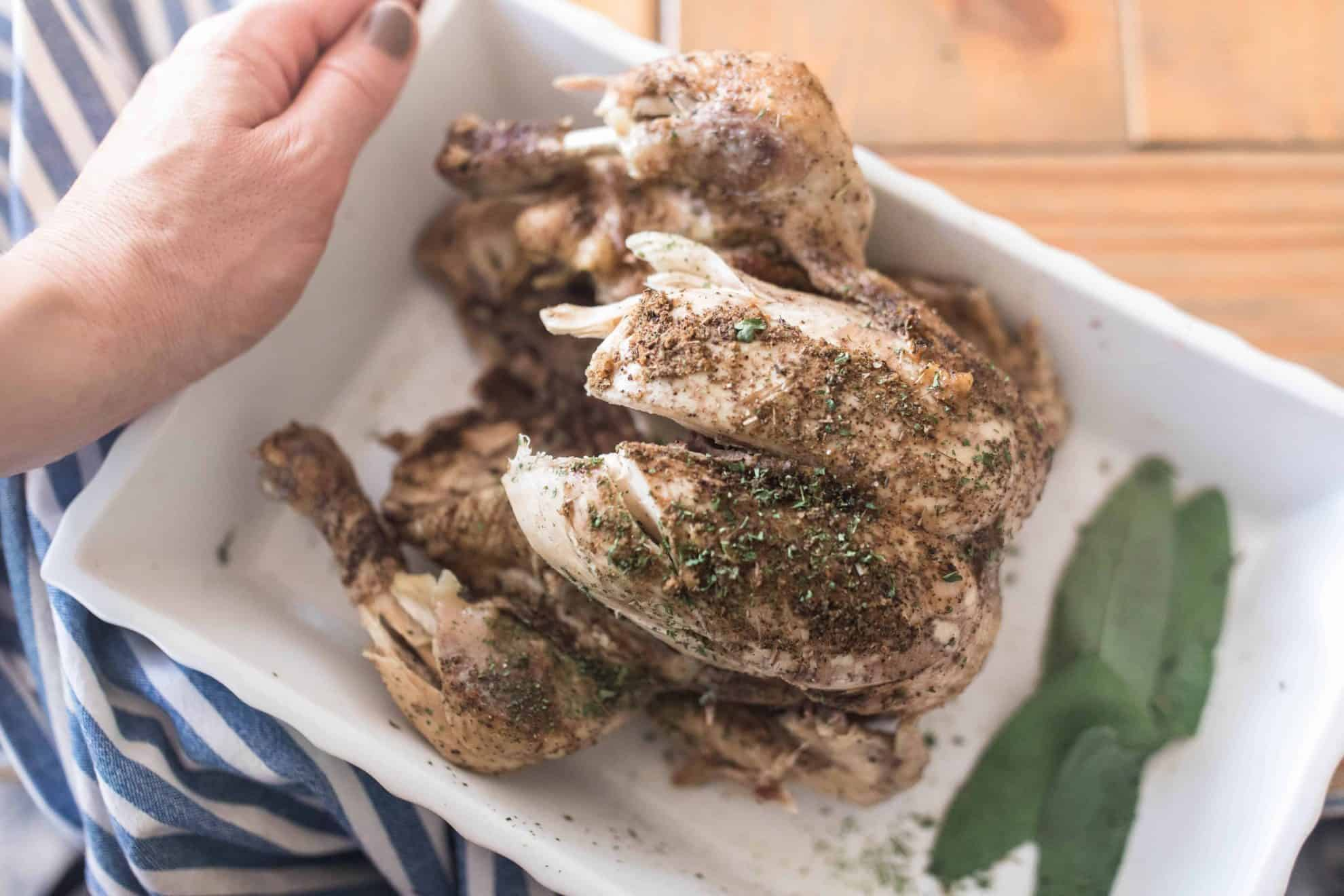 Instant Pot Whole chicken on a white platter with bay leaves