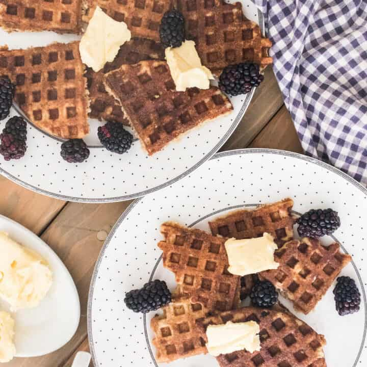 two plates full of sourdough waffles topped with butter and blackberries and a blue and white checkered towel hind it