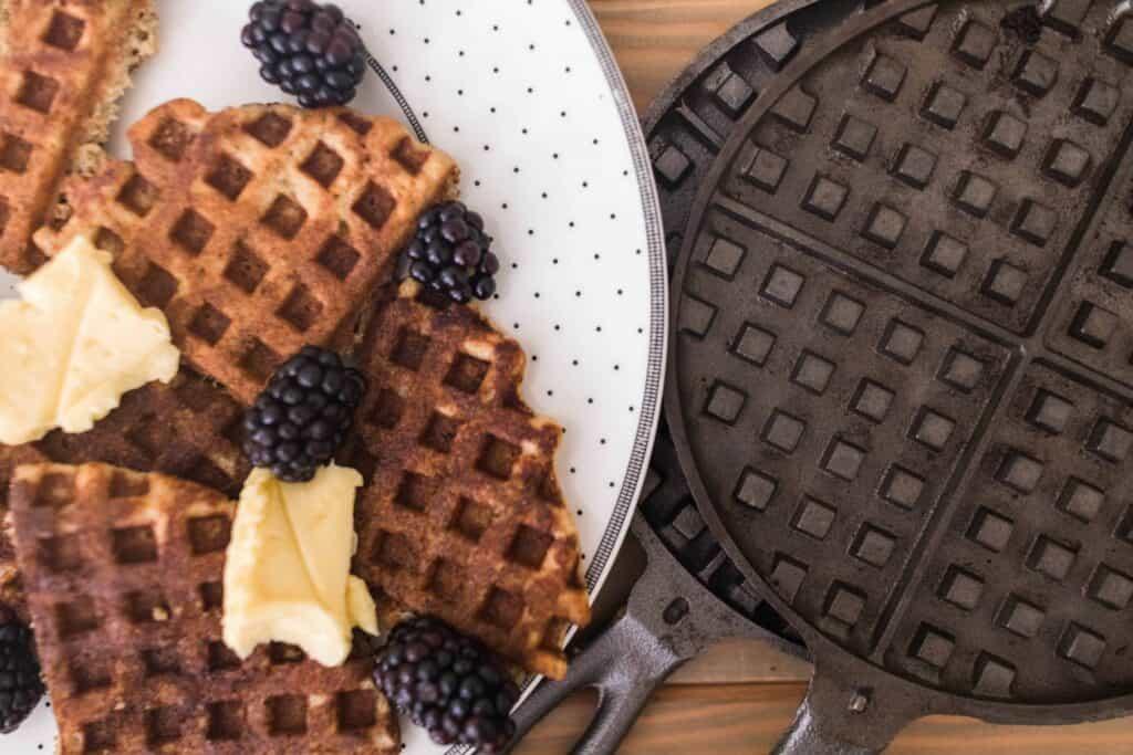 sourdough waffles on a white plate next to cast iron waffle maker