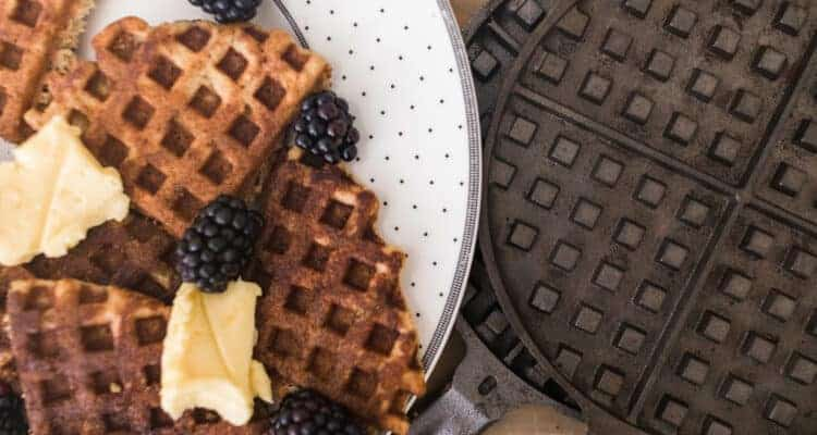sourdough waffles on a white plate next to cast iron waffle maker