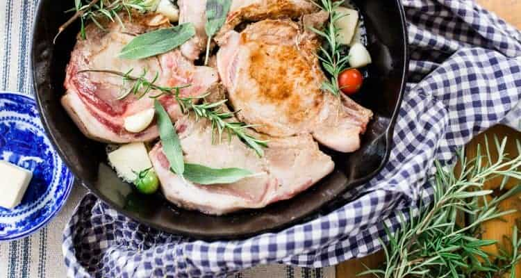 skillet pork chops in a cast iron skillet with fresh herbs on a blue and white towel