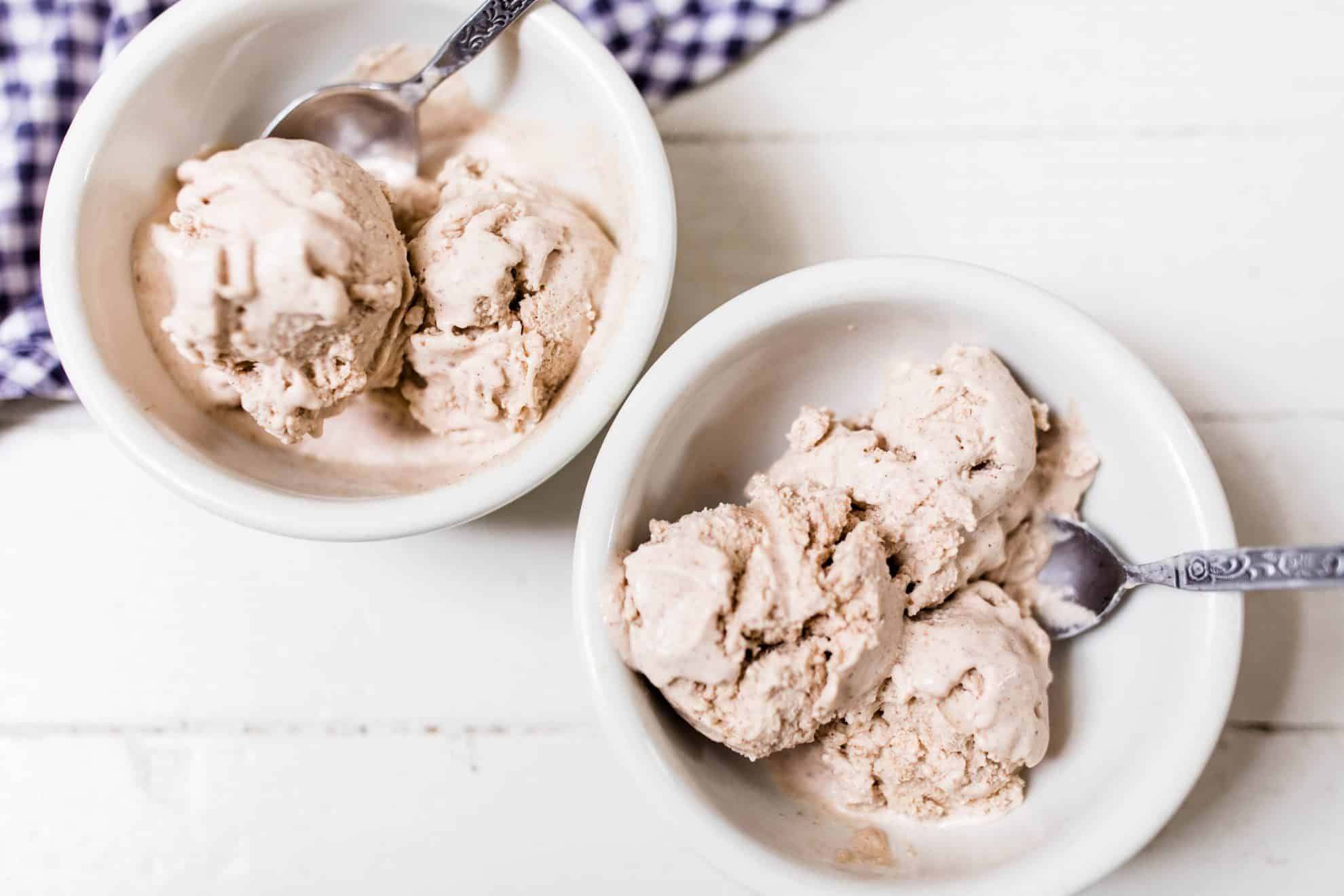 two bowls of pumpkin spice icecream on a white countertop with blue and white towel