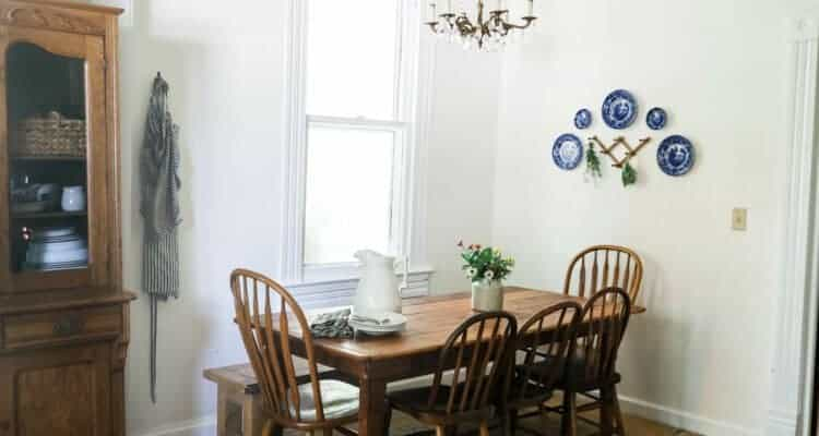 wide shot of farmhouse kitchen table and antique chairs with an antique cabinet full of collected dishes, with a plate wall to the right.