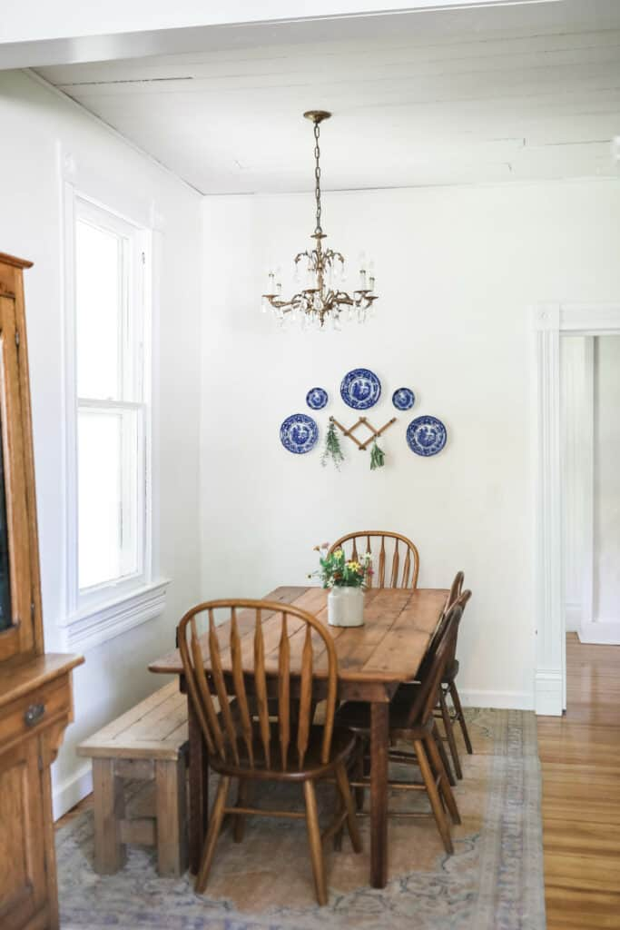 farmhouse eat-in kitchen with farmhouse table with antique chairs on a vintage rug next to a wooden antique hutch