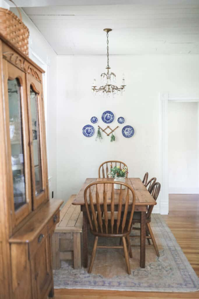 Farmhouse kitchen table with wood chairs and a blue and white plate wall