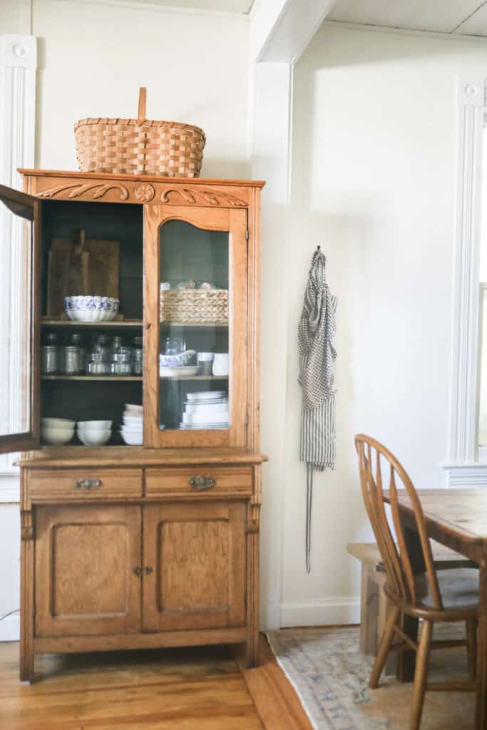 antique hutch filled with plates and jars with a door open. Aprons hanging to the right and the corner of a table and chairs on top of vintage rug =.