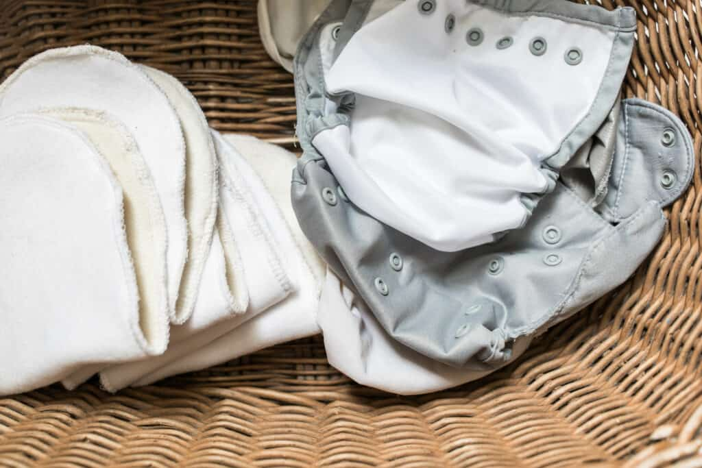 DIY cloth diaper inserts and a gray diaper cover in a wicker laundry basket