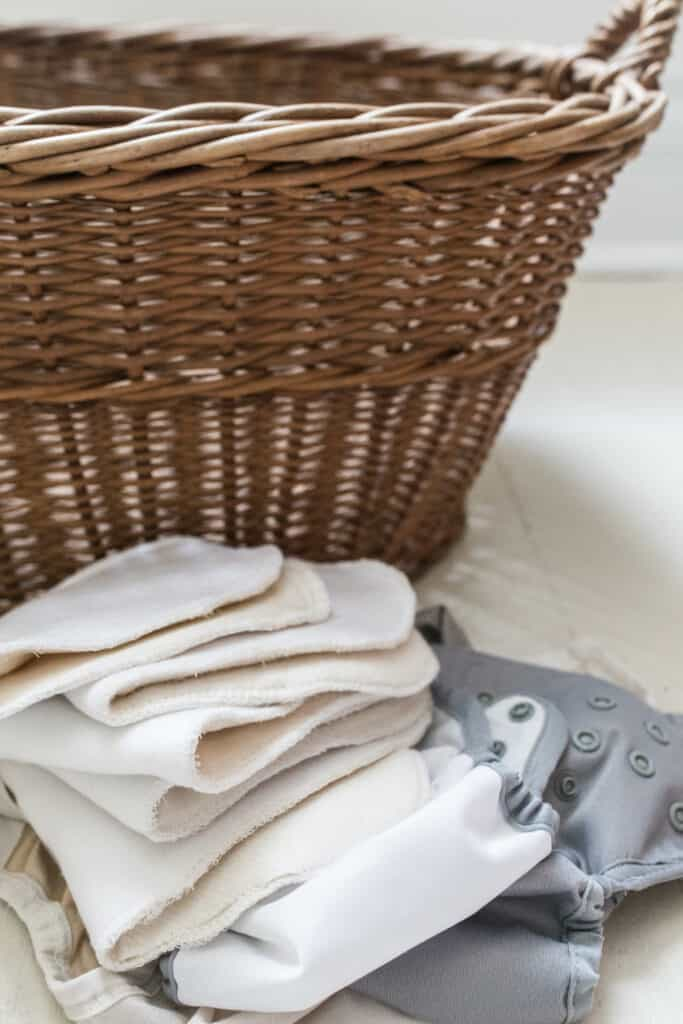 DIY cloth diaper inserts stacked up next to a wicker woven laundry basket