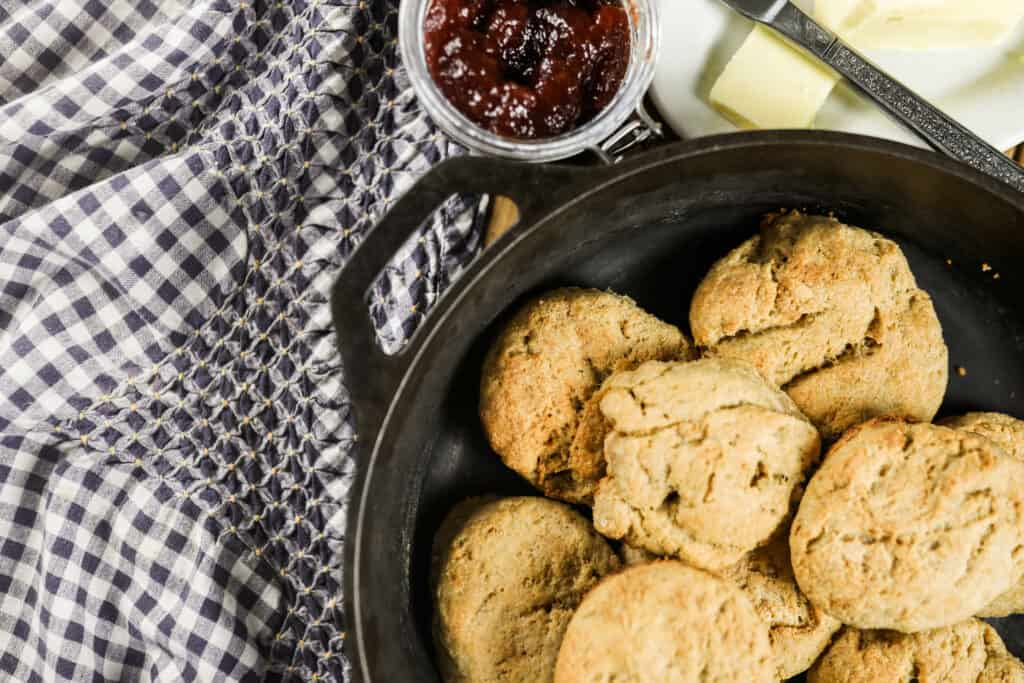 biscuits in cast iron skillet on a blue and white towel with jam in a jar