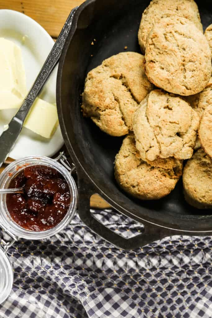 sourdough biscuits in a cast iron skillet with butter and jam to the left