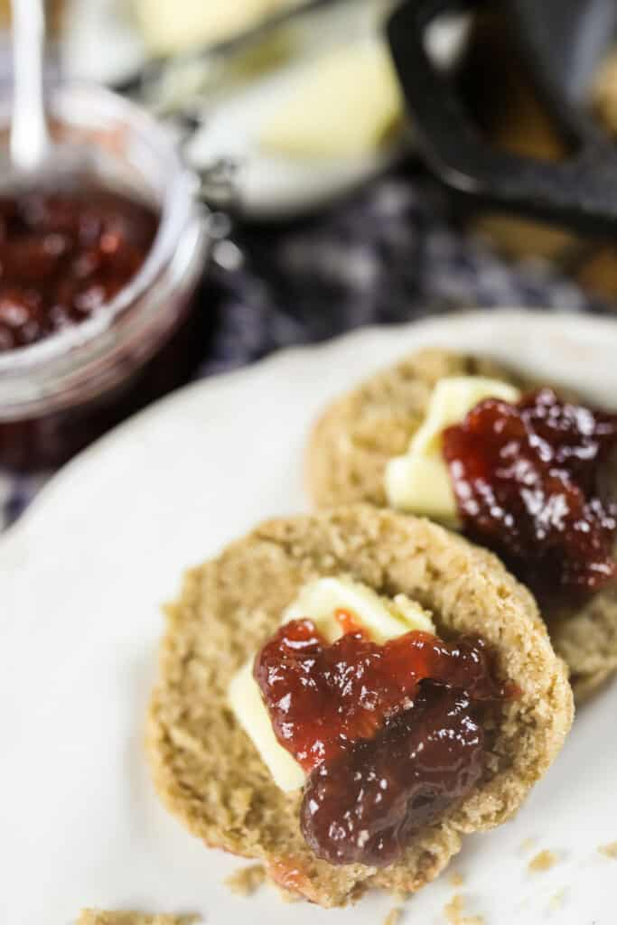 long fermented sourdough biscuits sliced in half with jam and butter on top on a white plate