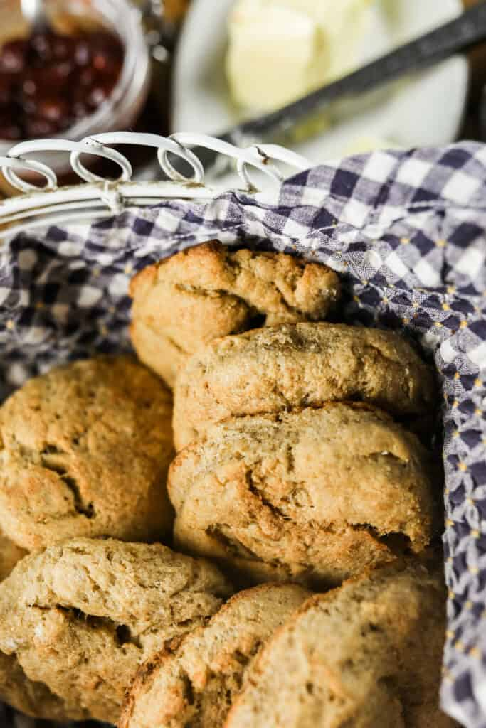 long fermented sourdough biscuits in a basket lined with a blue and white checked towel