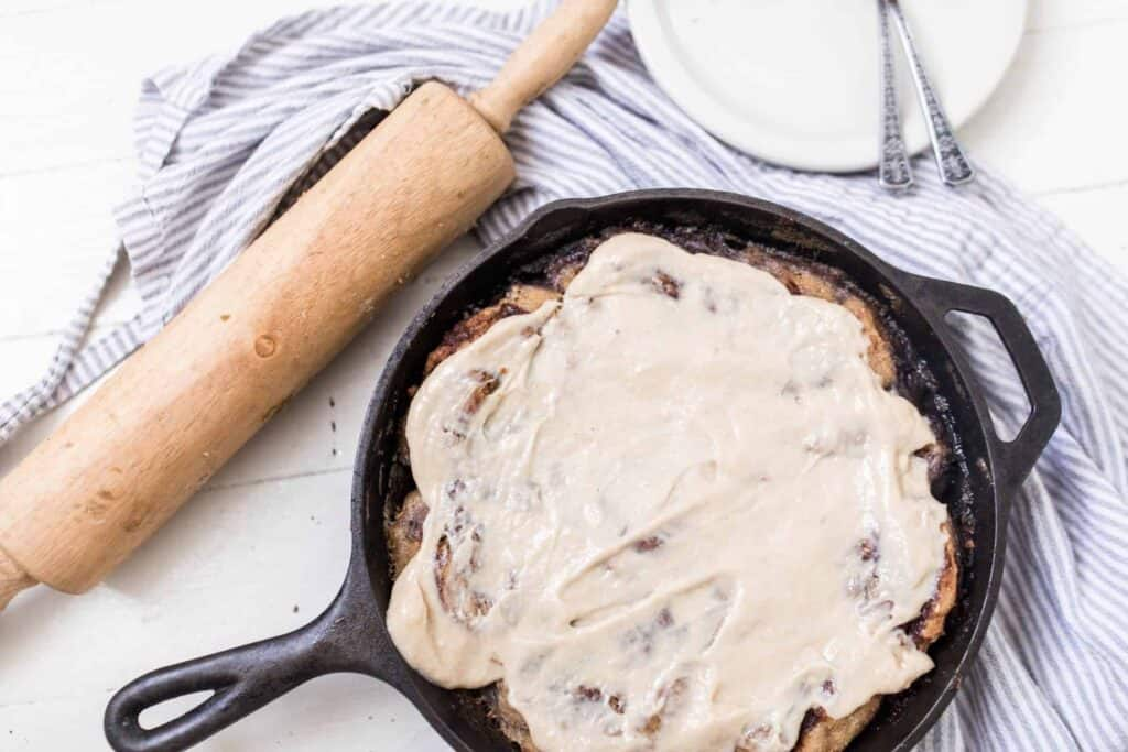 cast iron skillet with sourdough cinnamon rolls covered in cream cheese topping on top a blue towel with a rolling pin to the left