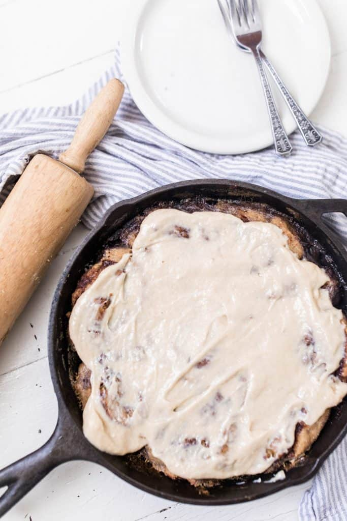 cast iron skillet with freshly baked sourdough cinnamon rolls covered in cream cheese topping on top a blue and white stripped towel
