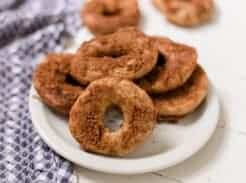 sourdough donuts covered in cinnamon sugar stacked on a white plate. A blue and white towel is to the left